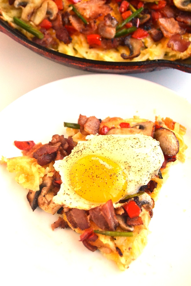 Breakfast Pizza with Hash Brown Crust has a crispy, cheesy hash brown crust and is topped with , eggs, bacon, melted cheddar cheese, and sauteed mushrooms, asparagus and peppers! www.nutritionistreviews.com
