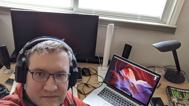 Selfie of the author, wearing a gamer headset in front of a desk artfully messy with computers and programming books.