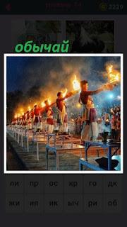 на столах стоят мужчины и согласно обычая держат огонь в руках