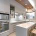 Cozinha retangular com ilha decorada com cores neutras e madeira!