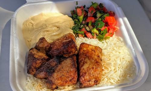 Pork shish kabob plate with rice, salad, and hummus