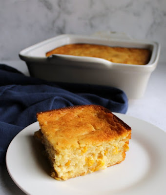 piece of corn casserole on plate in front of square baking dish filled with remaining corn pudding