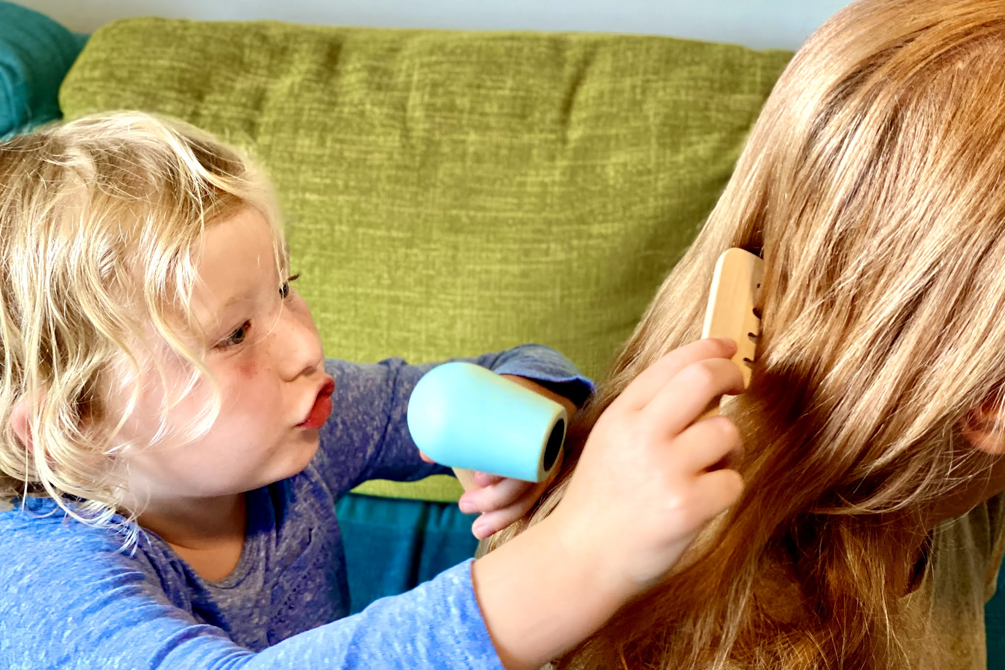 A child using a wooden hairdryer and comb received from luna and cash ethical online store for children