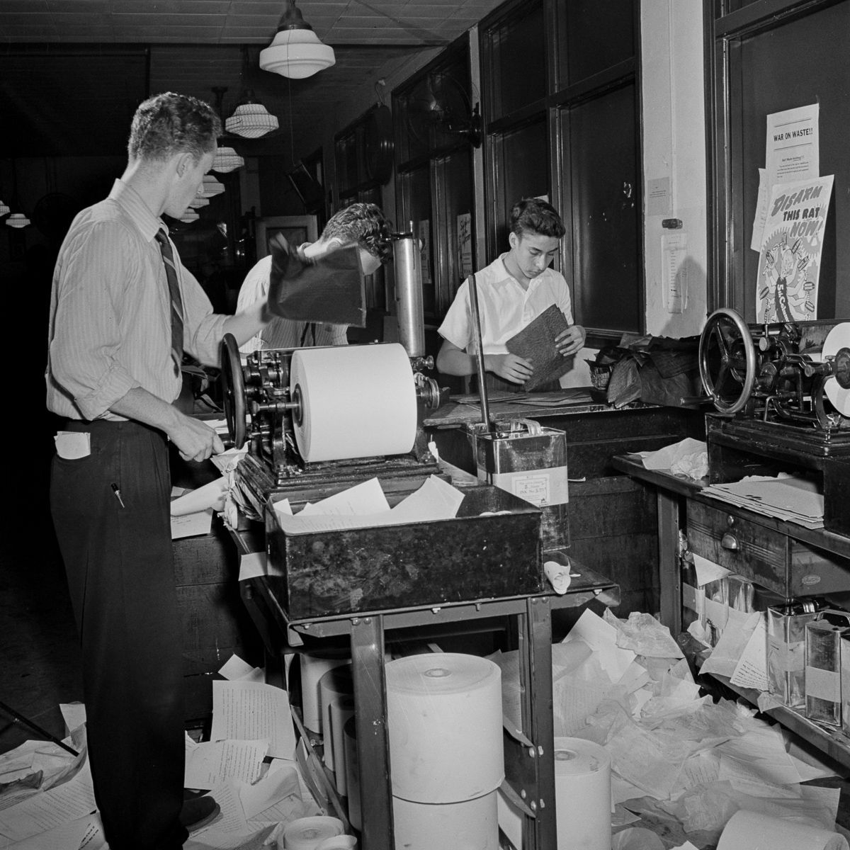 Copy boys mimeograph the dispatches from the telegraphs and pass them through a slot to the newsroom, where they are sorted and distributed to the various desks.