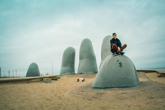 Homem sentando em uma escultura de dedos gigantes enterrados na areia