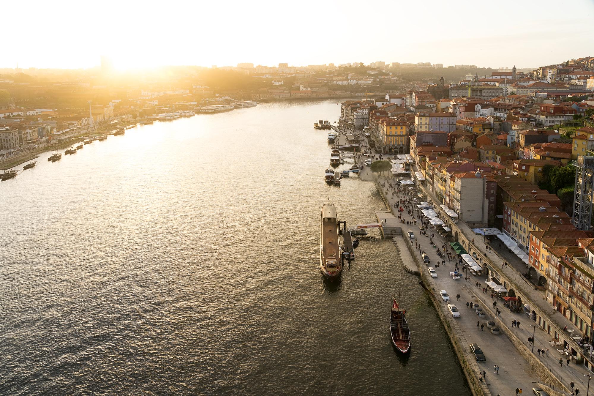 Porto al atardecer desde el puente de Luis I, con el sol en el fondo y la zona de A Ribeira en primer plano.