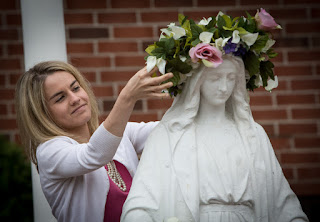 A woman crowning a statue of Mother Mary with a crown of flowers