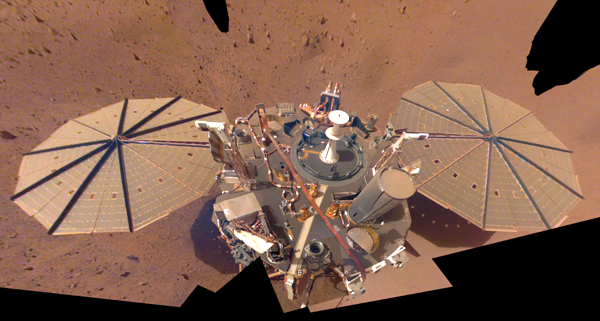 A composite image of the InSight Mars lander that was taken with its robotic arm camera on March 15 and April 11, 2021.