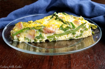 side view of frittata with chunks of ham and stalks of asparagus showing through eggs