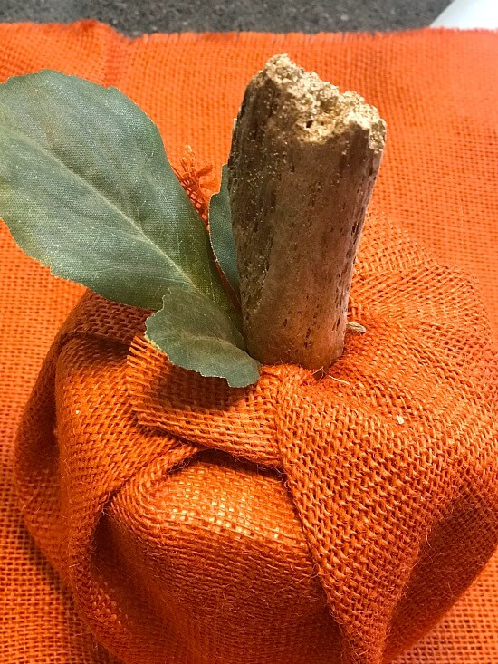 Stick and leaf sticking out of top of orange burlap toilet paper cover.