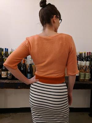 woman wearing a cropped shirt, facing away