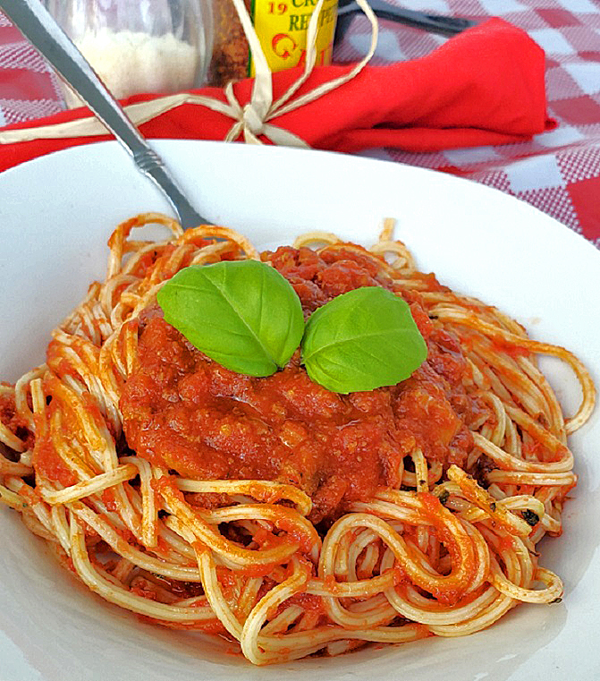 this is spagehtti topped with ragu sauce with basil