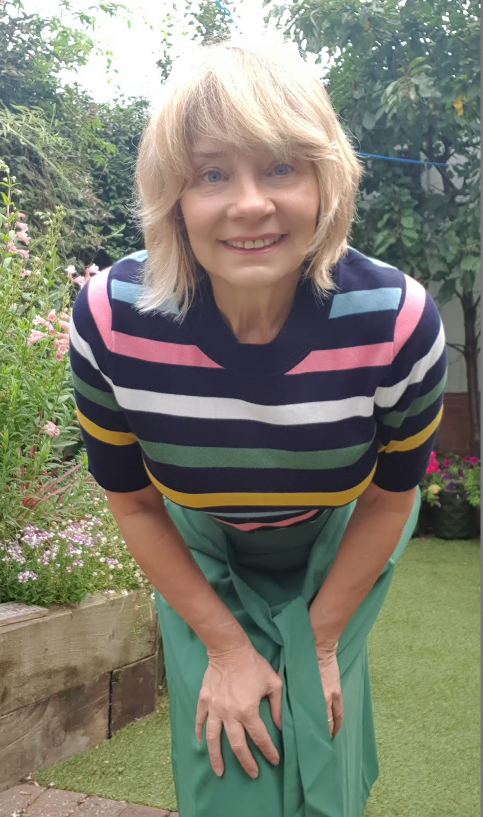 Mid life blogger Gail Hanlon from Is This Mutton in striped knit top and green midi skirt from Boden