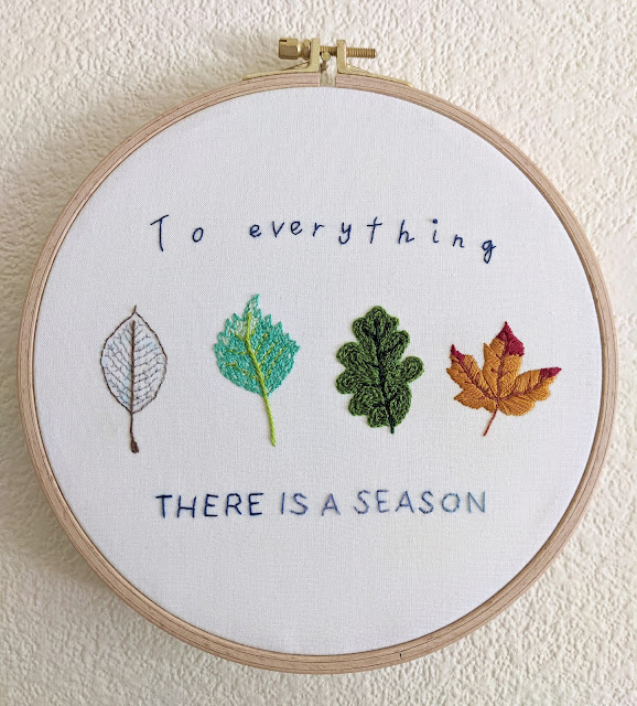 embroidery hoop with four embroidered leaves representing each season and stitched text To everything there is a season