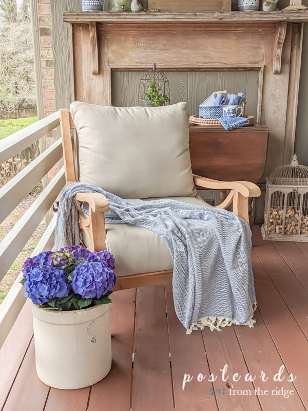 blue hydrangeas and teak outdoor chairs on deck for spring
