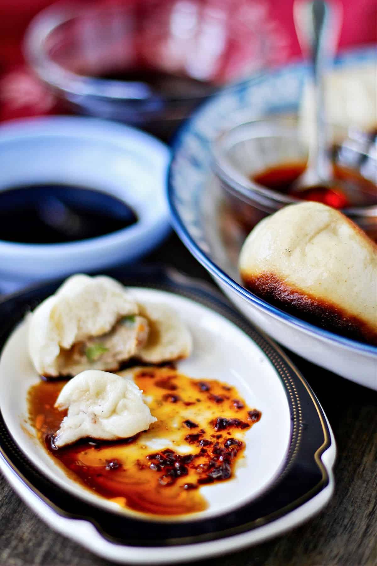Pan Fried Pork and Scallion Buns (Shēng Jiān Bāo)  with dipping sauce.