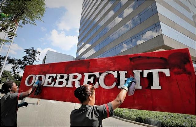 Faxineiras limpam o letreiro da sede da Odebrecht em SP