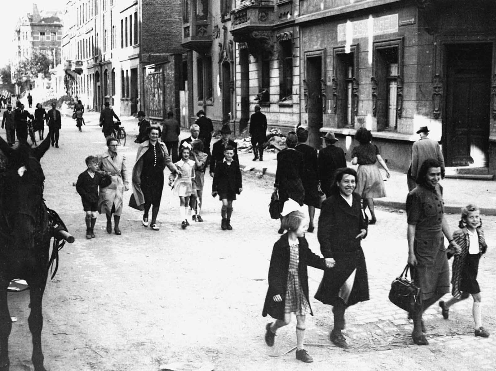 German mothers walk their children to school through the streets of Aachen, Germany, on June 6, 1945, for registration at the first public school to be opened by the U.S. military government after the war.