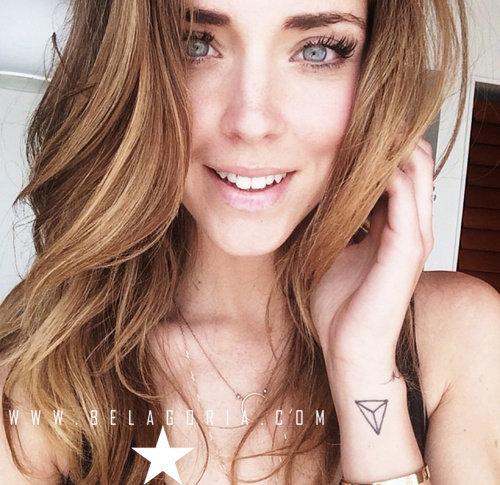 Foto de chica sonriendo, lleva tatuaje en la muñeca