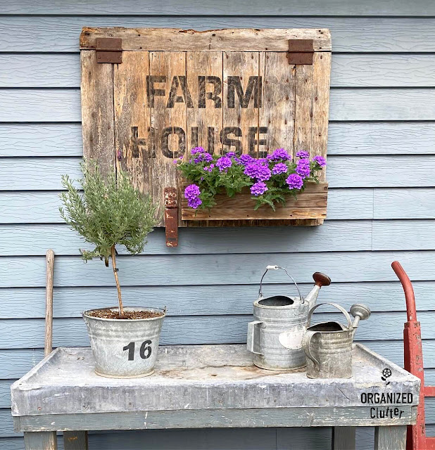 Photo of a potting bench with lavender topiary and watering cans, farmhouse sign/planter