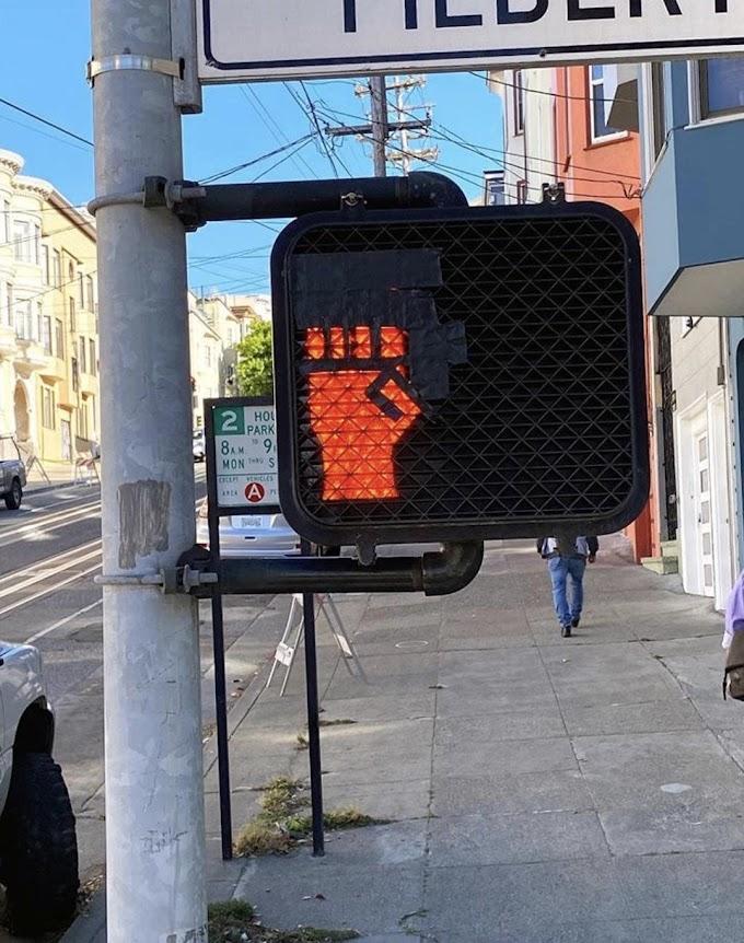 黒いテープを貼るだけの簡単な作業で、横断歩道の赤信号を「人種差別反対」のシグナルに変えたナイスなアイディアのストリート・アート‼️