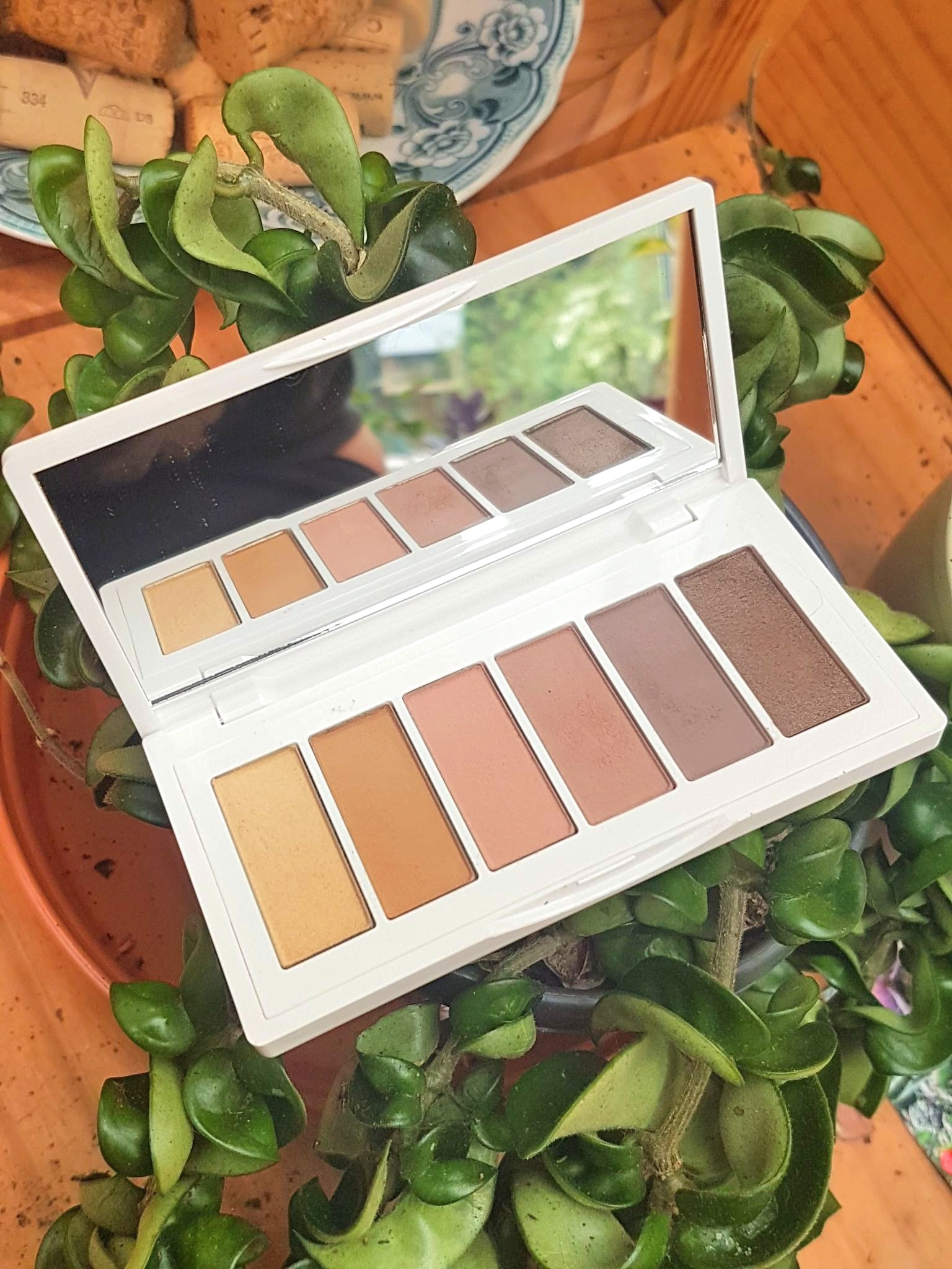 Ere Perez Chamomile Eyeshadow Palette in shade Lovely open on top of a green trailing hoya plant