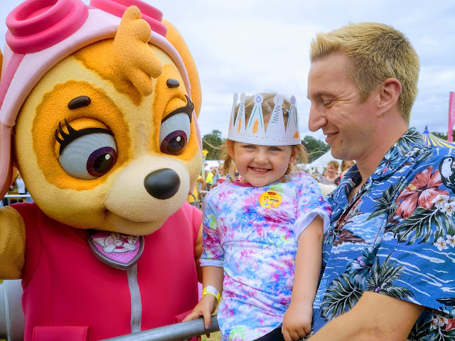 Image of a young girl in a tie dye top and plaited hair meeting Skye the pilot Paw Patrol character. Skye is wearing a pink flying suit and has pink flying goggles on her head. The girl is smiling. She is being held up by a man in a Hawaiian shirt.