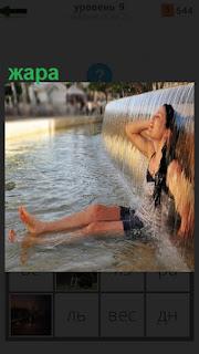 Девушка под фонтаном воды в жару спряталась и сидит с протянутыми ногами