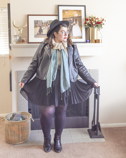 An outfit consisting of a wide brim hat, black moto jacket over a cream cowl neck sweater with a seafoam colored scarf tied under the cowl, black pleated skirt and black boots.