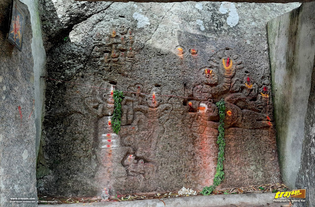 Some carvings of Hindu deities Lord Shiva, Lord Vishnu, and their divine animals, Nandi the bull and Shesha Naga the serpent, respectively, on a rock surface in Devarayanadurga