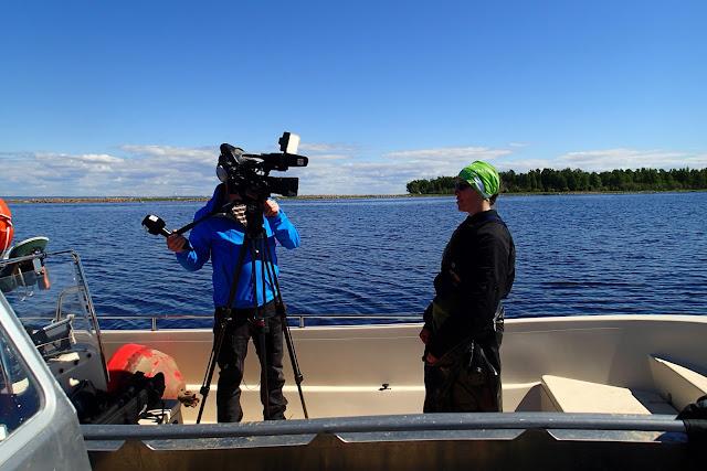 YLEn toimittaja kameran takana ja Essi sen edessä veneessä.