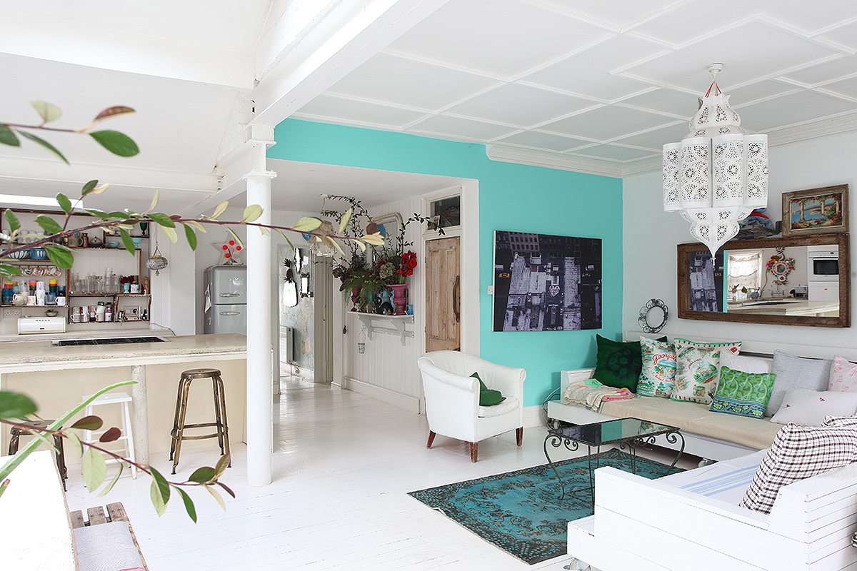 bohemian interior living room, houseplants, white floors and rustic furniture