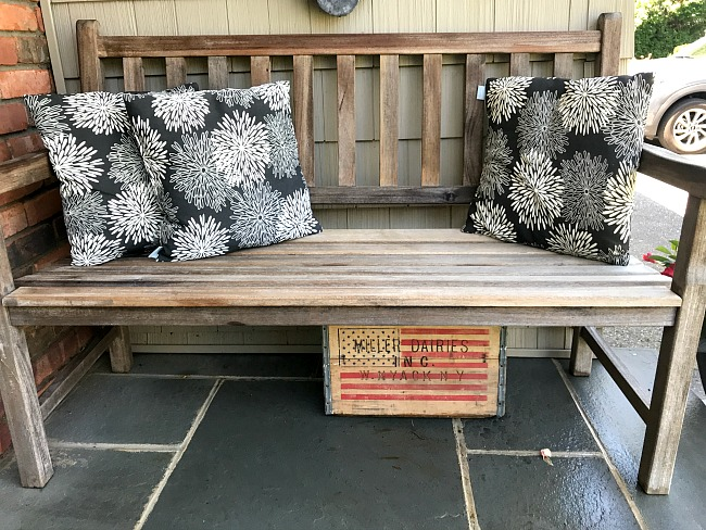 teak bench with flowered pillows