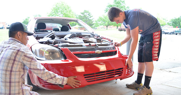 students attach a front bumper on a red automobile