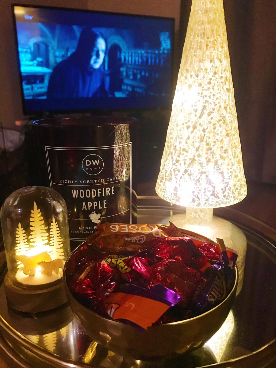 harry potter on tv in background. Gold metal tray on coffee table with light up tree, woodfire apple candle, light up globe and bowl of xmas chocolates
