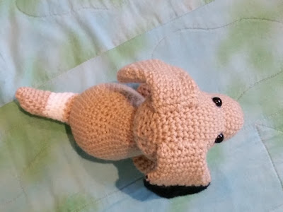 Above-view of crocheted dog. The light brown dog is sitting on mottled blue-green fabric facing towards the right hand side.  The tail has a white patch close to the body and is pointing to the left. The dog has a rounded body with a cylindrical head. Two teardrop shaped, floppy ears are attached on the top of the head