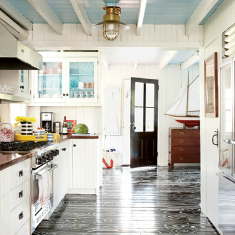 Coastal kitchen with light blue ceiling and painted wood grain floor