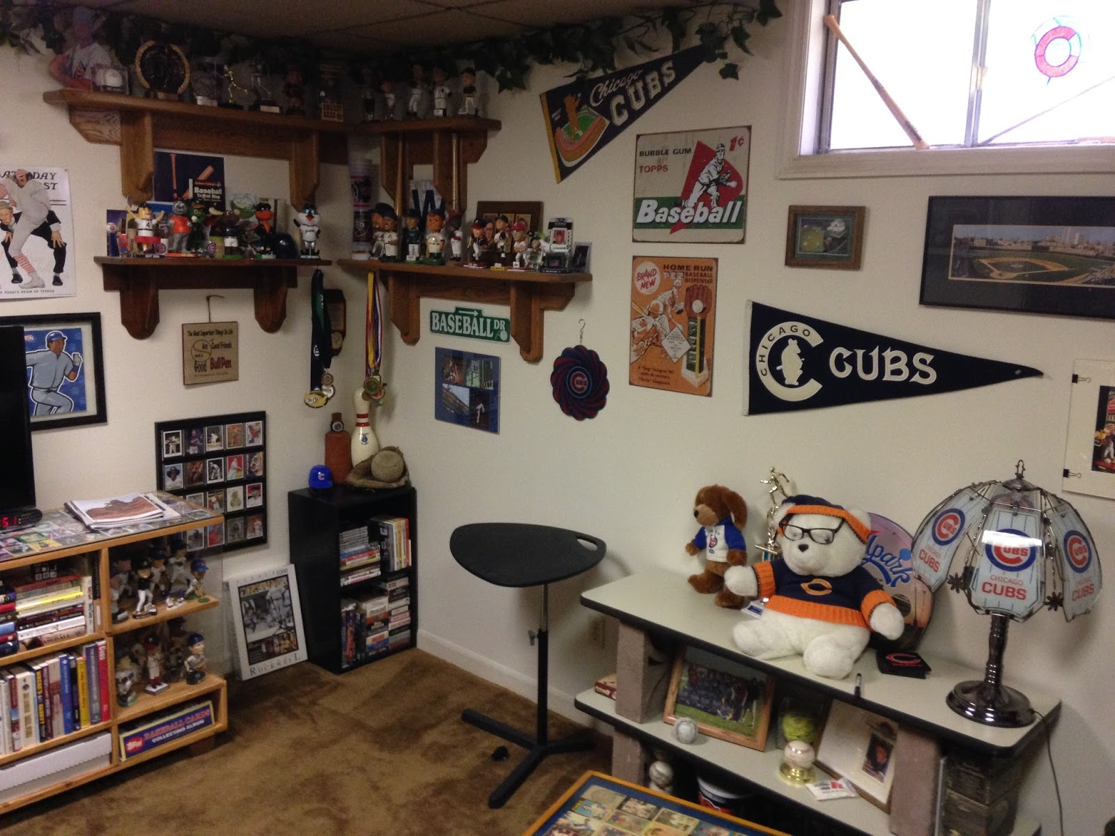 There Are Bobbleheads On The Shelves In Upper Left Corner And Baseball Movies VHS Within Black Shelving Unit Floor