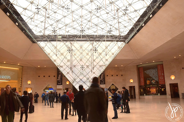 people inside museum, inverted pyramid from ceiling