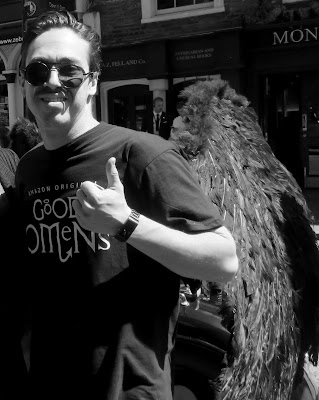 Black and white photo of a man whearing sunglasses, a black T short reading 'good omens' and black wings