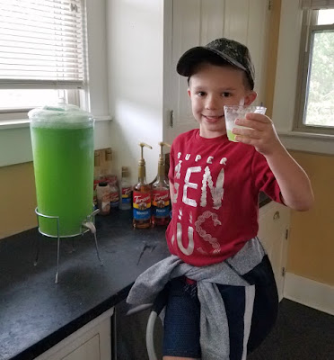 Little Dude standing next to a beverage dispenser with 2 gallons of green slime punch