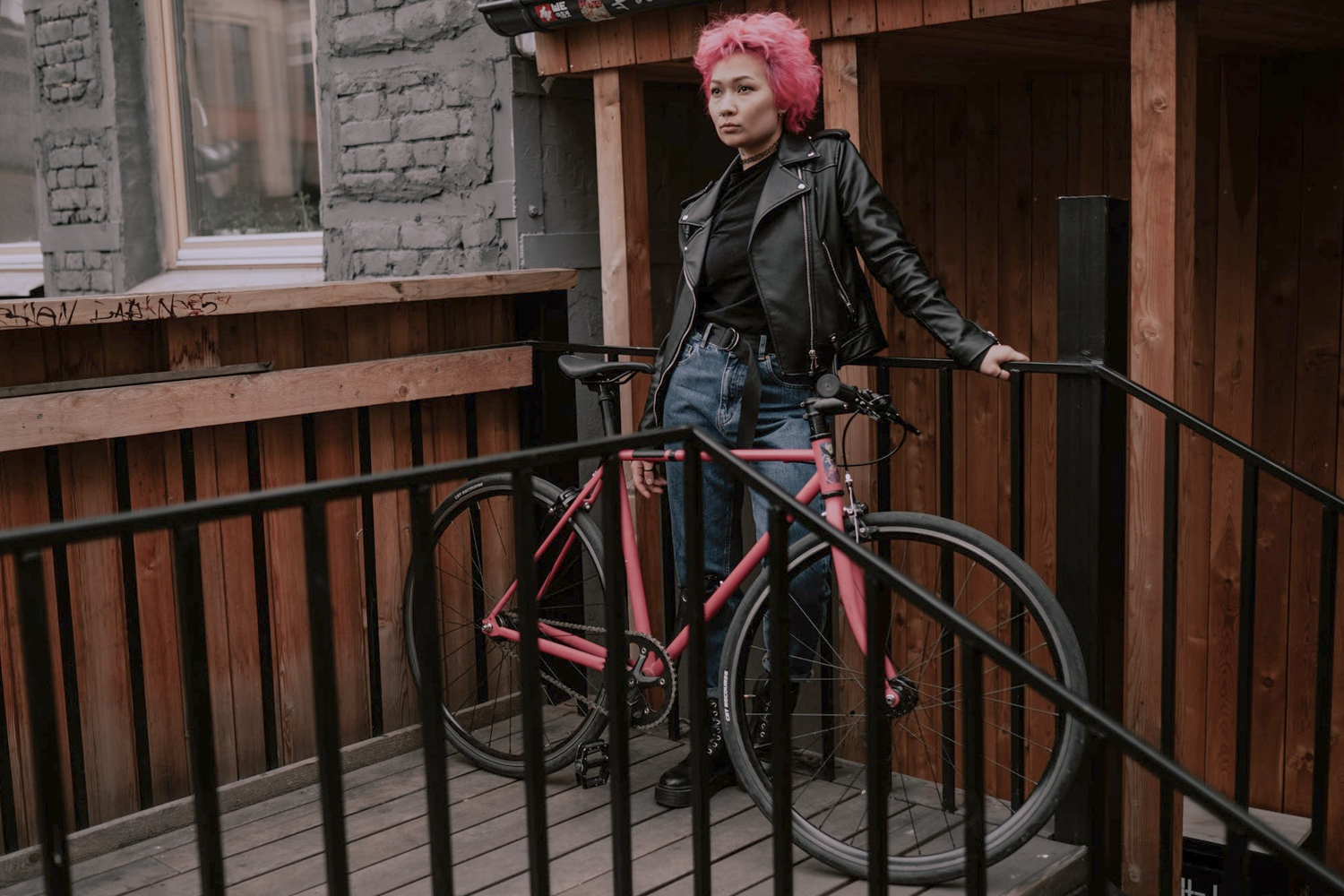 woman in a leather jacket is posing next to her bike