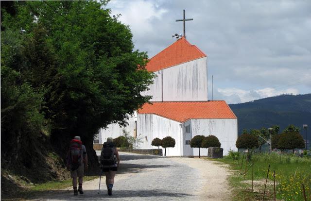 peregrinos de Santiago de Compostela caminhando em direção à uma igreja