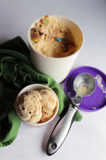 tub of monster cookie ice cream with scoop and some served ready to eat