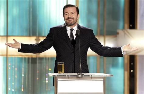 Ricky Gervais in tux on stage against backdrop of vertical lines and one thick, bright horizontal line aligning with his arms outstretched on both sides