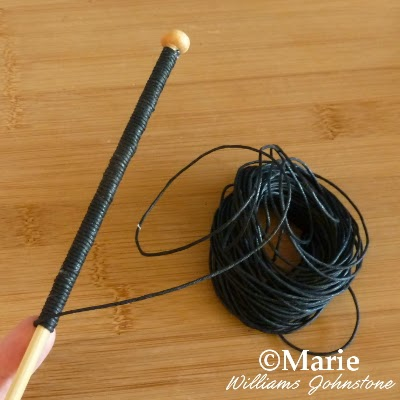 Black leather cord being wrapped around a wooden stick