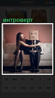 На диване сидит девушка, которая мужчине интроверту одела на голову коробку с нарисованным лицом