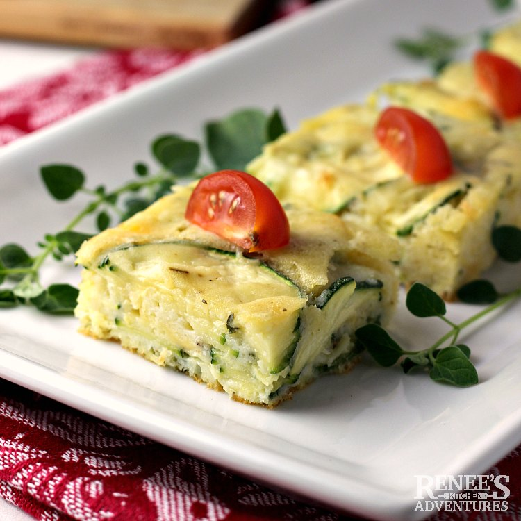 Zucchini Appetizer on a white serving plate garnished with fresh oregano and cherry tomatoes.