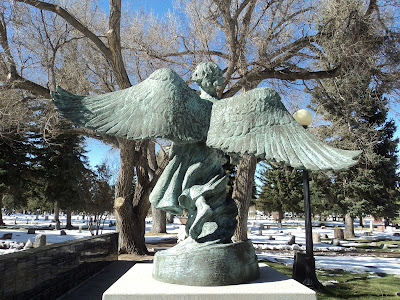 Stone statue of angel in cemetery, wings spread, seen frm behind