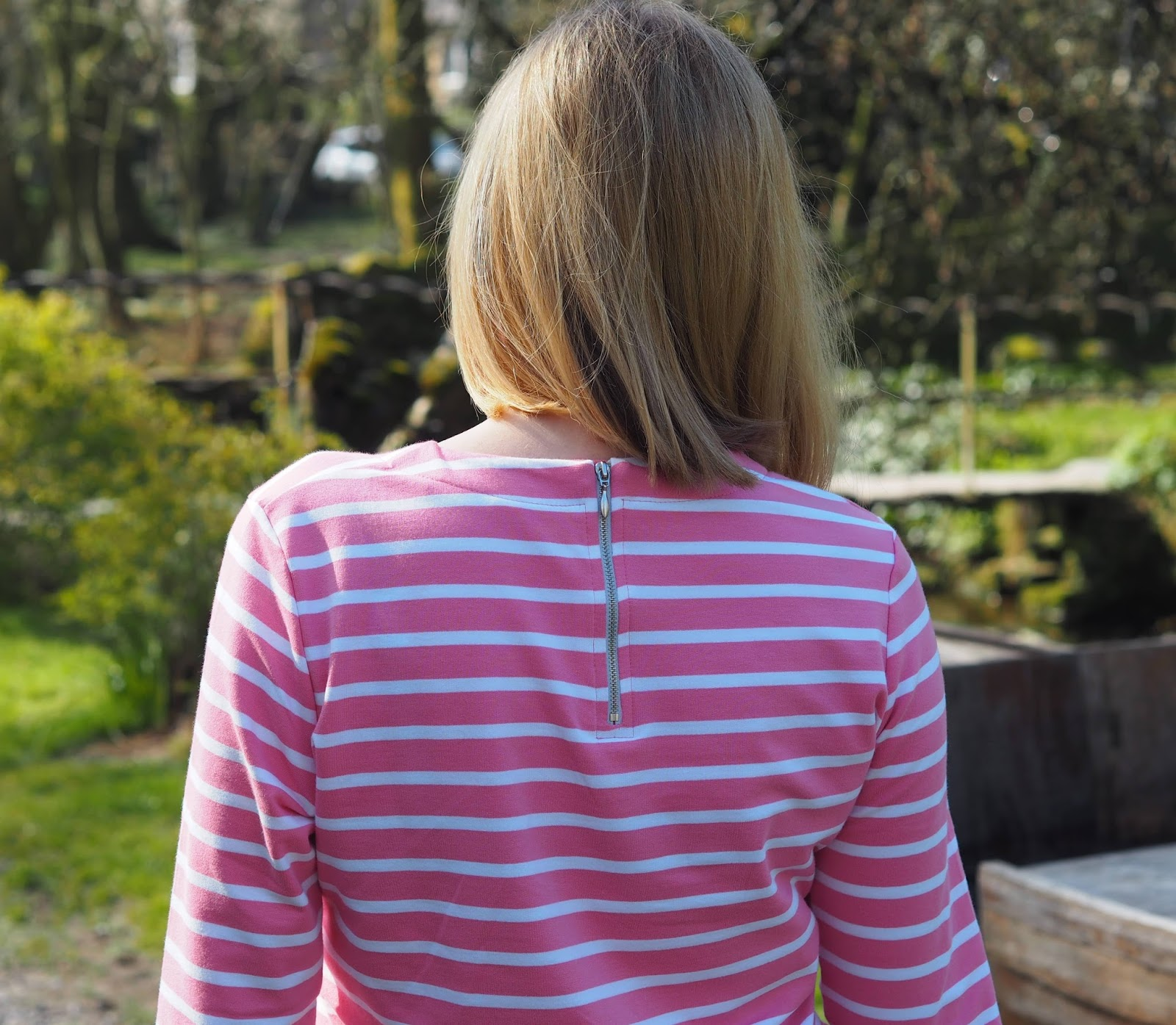 Back view including the zip on pink and white striped breton top by Tulchan with skinny jeans and silver Superga pumps